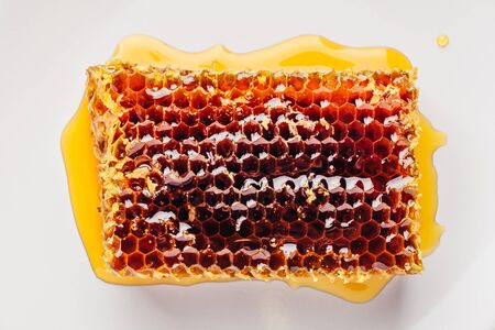 Top view of delicious yummy honeycomb on bright plate over light wooden