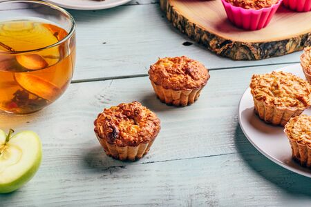 Healthy Breakfast. Cooked oatmeal muffins with apple and cup of green tea over light wooden 写真素材