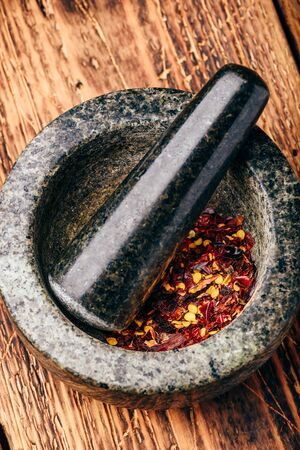 Red chili pepper grinded in stone mortar