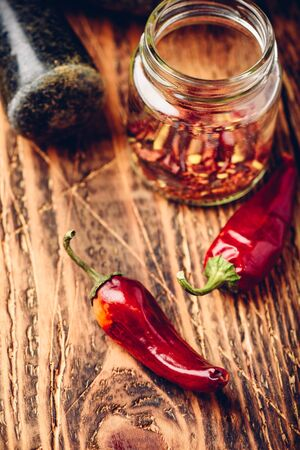 Sun dried red chili peppers on wooden surface