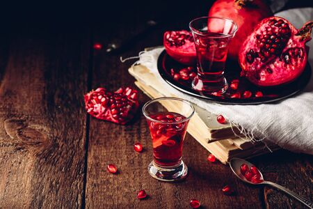 Shot glass of pomegranate cocktail with vodka, juice and fresh fruits