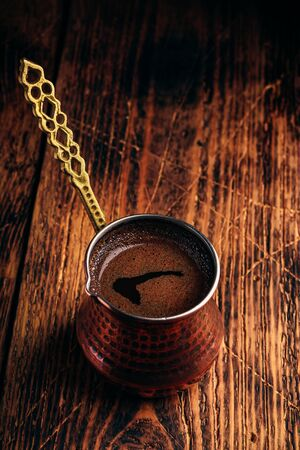 Turkish coffee. Brewed coffee in copper cezve on wooden surface