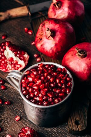 Metal rustic mug full of pomegranate seeds. Whole fruits and pomegranate pieces on dark wooden surface.