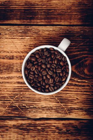 Roasted coffee beans in cup over wooden surface