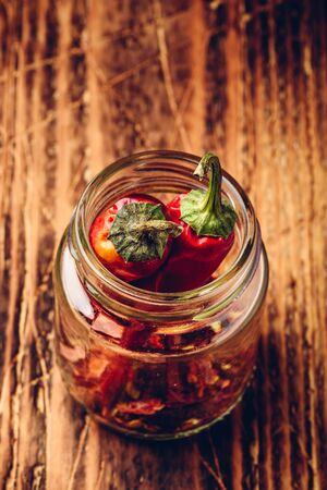 Two dried red chili peppers in jar with ground peppers