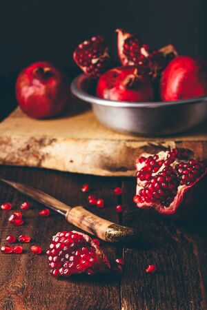 Pomegranate fruits with knife on rustic wooden surface.