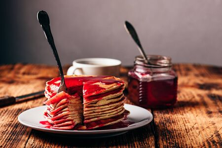 Stack of american pancakes with red berry jam on plate over rustic surface