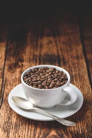 Roasted coffee beans in white cup over rustic wooden surface