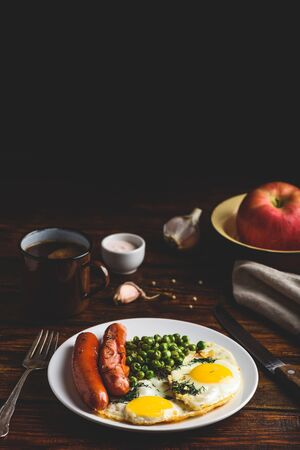 Breakfast with fried eggs, sausages and green peas on white plate