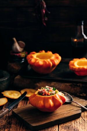 Fresh pattypan squash filled with minced beef on rustic cutting board