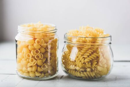 Two kinds of Italian whole wheat pasta in glass jars 写真素材