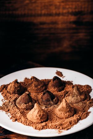 Homemade chocolate truffles coated in cocoa powder on white plate