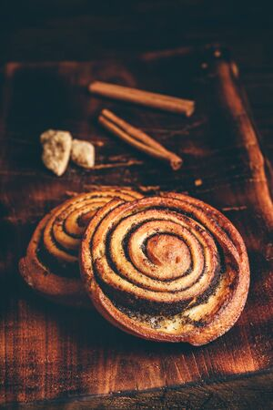 Sweet roll with poppy seeds on rustic wooden surface Reklamní fotografie