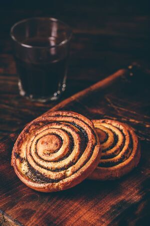 Sweet roll with poppy seeds. Glass of black coffee