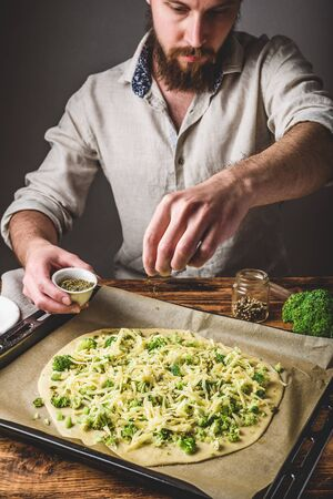 Bearded man pours spices on pizza with broccoli, pesto sauce and cheese Stockfoto
