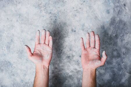 Man hands covered with paint on gray concrete wall