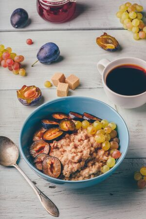 Healthy breakfast concept. Porridge with fresh plum, green grapes and cup of coffee.