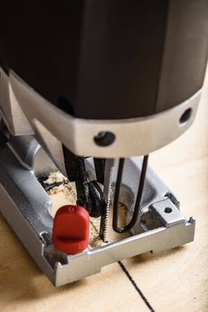 Electric jig saw cutting plywood. Close up