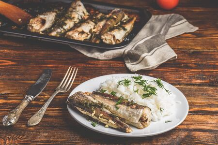 Baked hake carcasses with rice on white plate Фото со стока