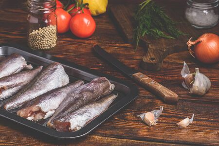 Hake carcasses on baking sheet with vegetables and spices Фото со стока