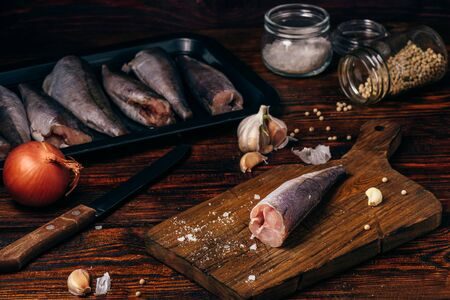 Hake carcasses on cutting board with spices and vegetables