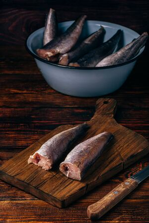 Hake carcasses on cutting board with knife and bowl over wooden surface Фото со стока