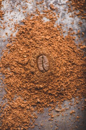 Fresh roasted coffee bean lays on heap of ground coffee