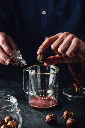 Steeping tea. Putting tea leaves into glass mug Фото со стока