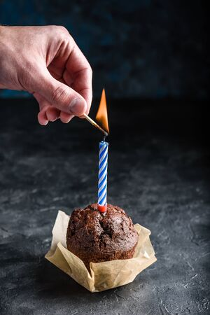 Hand lighting candle with a match on birthday chocolate muffin