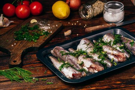 Hake carcasses on baking sheet with vegetables and spices Zdjęcie Seryjne