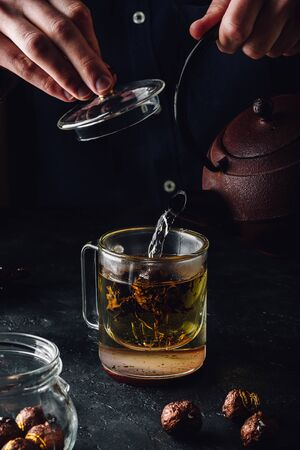 Steeping red tea in glass mug. Pouring boiled water from iron kettle. Фото со стока