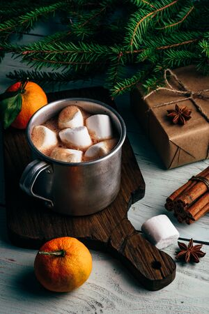 Rustic mug of hot chocolate with marshmallows. Christmas gift and tangerines on wooden table Stock fotó