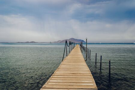 Old wooden pier on the Red sea at overcast day