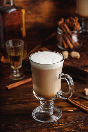 Irish coffee in drinking glass on wooden surface