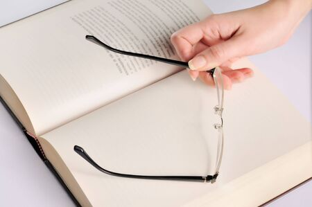 Woman hand with glasses on book Stock Photo - 6840869