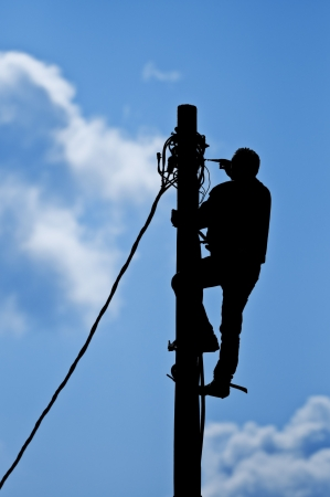 telephone pole: Black silhouette of man working on pole with natural sky in background