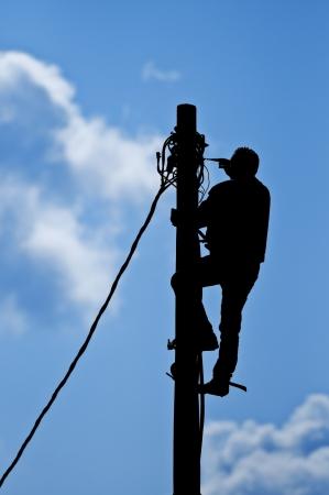 telegraaf: Zwart silhouet van man aan het werk op paal met natuurlijke hemel op achtergrond