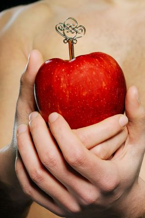 Man is holding red apple in hands with silver key Stock Photo - 6840902