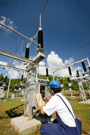 substation: Electrician repairing electric panel