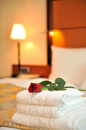 Room with red rose on bed
