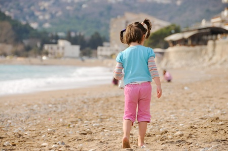pigtails: Young girl walking by the sea Stock Photo
