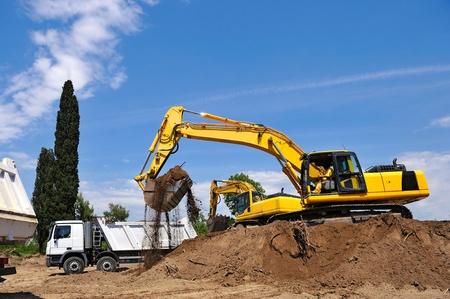 Excavator loading earth on truck photo