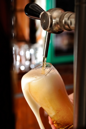 barman: Filling glass with beer Stock Photo