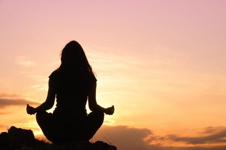 introspective: Woman meditation on the top of the hill Stock Photo
