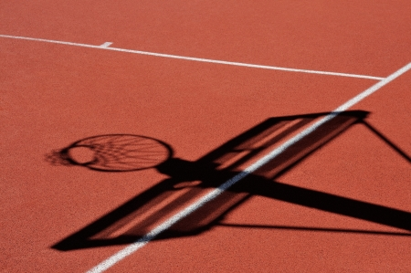 Basketball lines and shadow of basket on an outdoor court