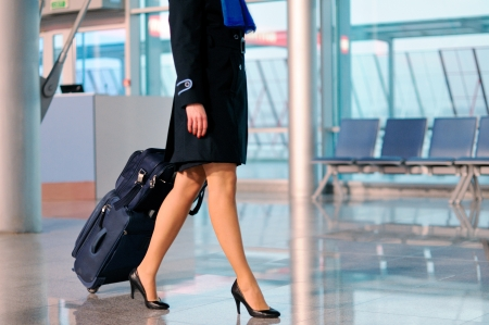 stewardess: Woman with bag at airport