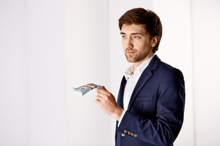 table skirt: Handsome confident young businessman standing near the office desk.  Hold the money. Looking at camera. Isolated on white background.
