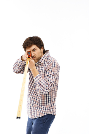 straight man: Close-up portrait of handsome confident young blue-eyed dark-haired man with tape measure wearing casual plaid shirt. Looking straight ahead. Isolated.