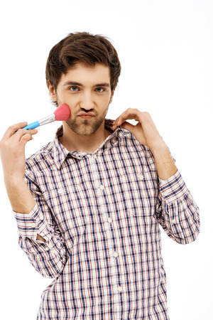 girlish: Close-up portrait of handsome romantic a bit girlish young blue-eyed dark-haired man with brush wearing casual plaid shirt. Isolated.