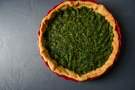 textural: Close-up photo of baked tart dough with spinach in red ceramic tart pan, over gray textural surface
